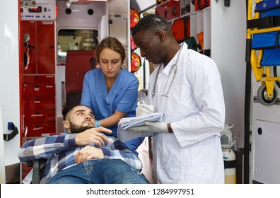 Paramedic giving patient logbook for signature in ambulance auto