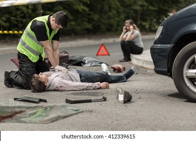 Paramedic resuscitating on street car accident victim, in the background woman talking on phone.