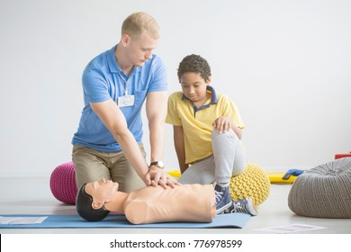 Paramedic showing first aid exercises on a manikin to an afro-american boy