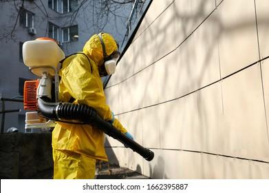 Paramedic wearing yellow protective costume and mask disinfecting coronavirus with the motorized backpack atomizer and sprayer, training. February 26, 2020. Kiev, Ukraine