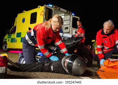 Paramedical team assisting injured man motorbike driver at night