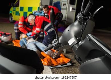 Paramedical team helping injured motorbike woman driver at night