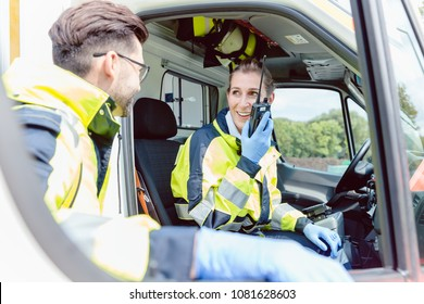 Paramedics in ambulance in radio contact with headquarters discussion deployment