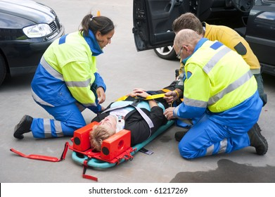 Paramedics and a fireman strapping a wounded woman  with a neck brace on a stretcher