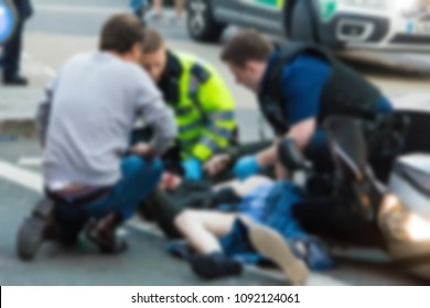 The paramedics and firemen provide first aid to victims in a motorcycle accident on Piccadilly Street. Blurred view