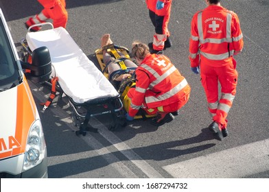 Paramedics give assistance to a girl lying on stretcher after a car motorcycle crash. Genova Italy october 30th 2015
