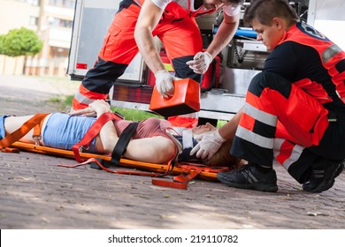 Paramedics giving first aid girl after accident