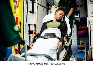 Paramedics moving a patient on a stretcher into an ambulance