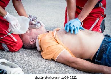 Paramedics succor a man with heart attack - Stock Image