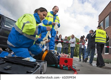 Paramedics tending to the first aid of an injured woman on a stretcher at the scene of a car crash, whilst a police woman is escorting a bystander towards the cordon tape, being filmed by a camera man