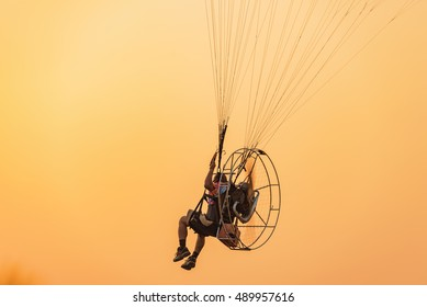 Paramotor flying on the sky  at sunset.