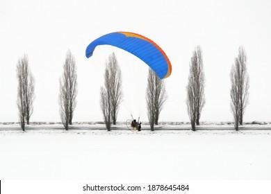 Le paramoteur vole en hiver dans un paysage blanc de neige et d'arbres noirs en contraste