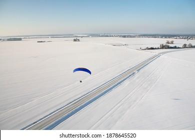 Un paramoteur photographié du ciel en hiver et suivant une route enneigée dans les champs d'Ile-de-France