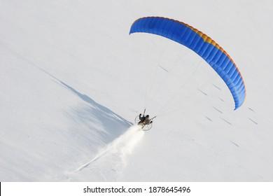 Un paramoteur vu du ciel en hiver volant à basse altitude et laissant un sentier dans la neige vierge