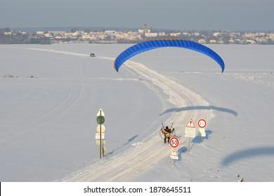 Un paramoteur vu du ciel en hiver volant à basse altitude au-dessus d'une route enneigée bordée de panneaux d'avertissement et d'une limite de vitesse à 50 kmh