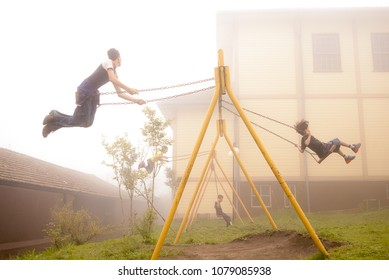 Paranapiacaba, Brazil. September 2, 2007. Children playing on a swing in playground during an afternoon with haze.