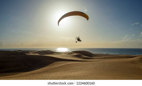 A paraplane flying over dunes at low height shot against the rising sun
