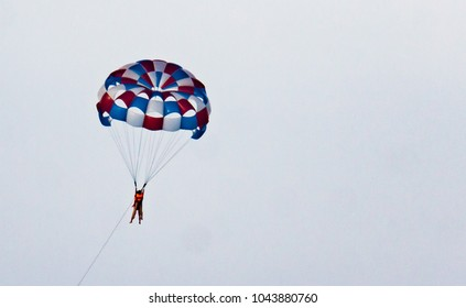 parasail with two swimmers hanging  being pulled by a motor boat