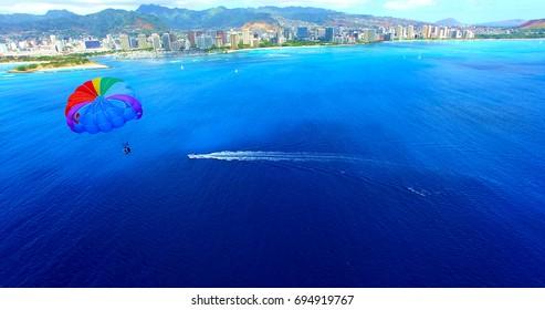 Parasailer With Rainbow Parachute Off The Coast of Honolulu/Waikiki Beach - Aerial Footage in Oahu, Hawaii