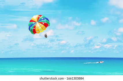 Parasailing above the ocean at tropical islands. Copy space, holiday fun activities.