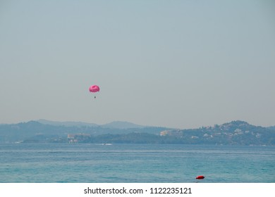 Parasailing at Beach in Europe, extreme Sport. Tourists parasailing, popular entertainment for holiday travelers on sea. Copy space