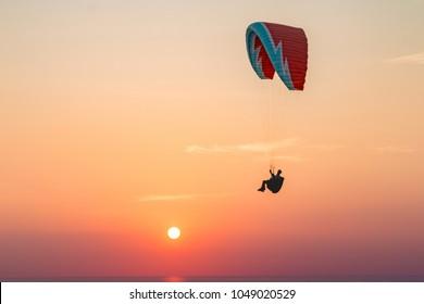 Parasailing behind sunset at  Windmill viewpoints, Phuket Thailand