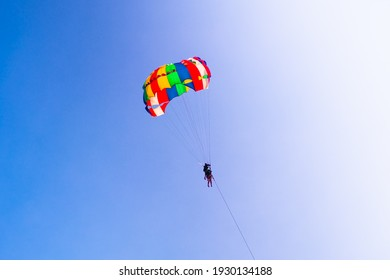 Parasailing in blue sky. Parachute sports, active leisure, travel, vacation concept. Freedom and active lifestyle
