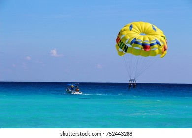 Parasailing on Caribbean sea in Cancun, Mexico - view on the beautiful turquoise sea and the yellow smiling parachute with two people in, November 2, 2017