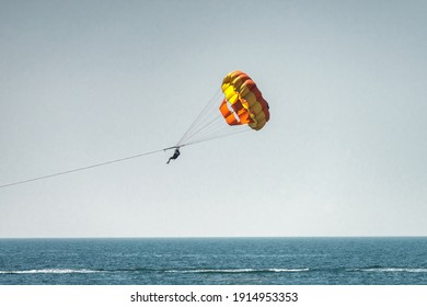 Parasailing on the sea, unrecognizable girl in blue sky, selective focus on person flying. Concept of vacation, extreme sports on a beach