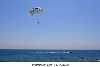 Parasailing, parachute in the sky and boat on the sea, fly over the sea