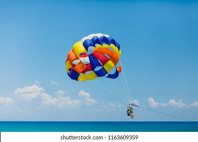 Parasailing water amusement - flying on a parachute behind a boat on a summer holiday by the sea in the resort