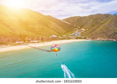 Parasailing water amusement. Flying on a parachute behind a boat on a summer holiday by the sea in Ky Co beach, Quy Nhon, Vietnam. Travel and sport concept. - Shutterstock ID 1831633003