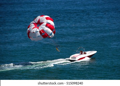 Parasailing water amusement. Flying on a parachute behind a boat on a summer holiday by the sea in the resort. Beautiful bright blue water and red and white parachute.
