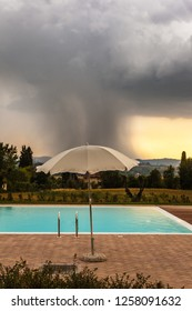 a parasol near the edge of a swimming pool and a storm in the background
