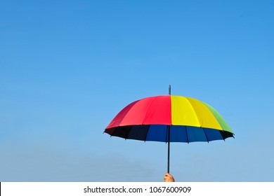 parasol.Rainbow umbrella on the blue sky. Use as background image.Many colorful umbrellas. concept:summer ,UV radiation, protected sunlight, Sunscreen ,safety