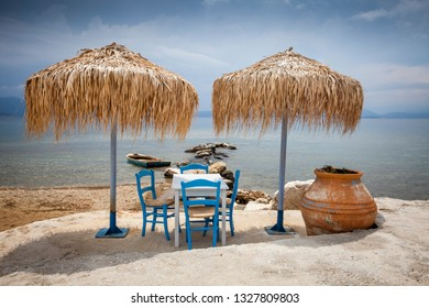 Parasols, table and chairs on the coastline of the greek peninsula Pilion