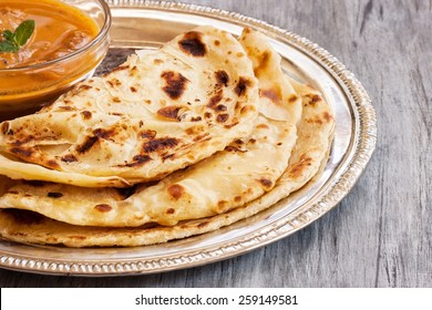 Paratha served with chicken curry close up selective focus