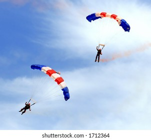 Paratroopers descending in a military skydiving parachute demonstration