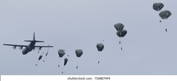 Paratroopers jump from C-130 Hercules military plane on evening