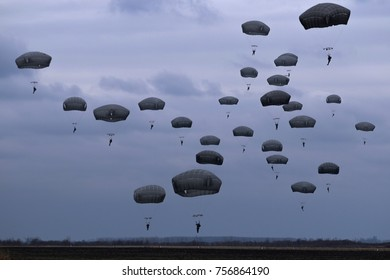 Paratroopers jump from military plane on evening