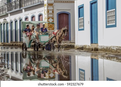 Paraty, Brazil February 26, 2017: The typical portuguese style colonial buildings and unidentified group of people on a carriage in the stone street in downtown of Paraty, Rio de Janeiro, Brazil.