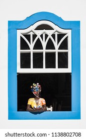 Paraty, Brazil - February 28, 2017: Traditional brazilian souvenir girl at the country house window in historic town Paraty, Rio de Janeiro state, Brazil