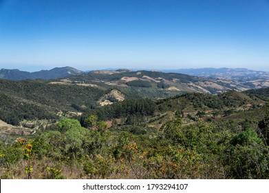 PARATY, RIO DE JANEIRO / BRAZIL - AUG 17, 2019: The surrounding mountainous green landscape under clear blue sky as saw from the Pedra da Macela viewing spots, inside Serra da Bocaina national park.
