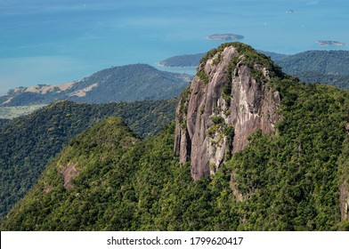 PARATY, RIO DE JANEIRO / BRAZIL - AUG 17, 2019: Closer view and detail of the rock formation peak covered with Serra do Mar green vegetation with Carioca bay coastline at the background.