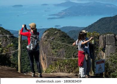 PARATY, RIO DE JANEIRO / BRAZIL - AUG 17, 2019: Tourists enjoying the mountainous Serra do Mar landscape at a rope fence on Pedra da Macela landmark with Carioca bay at far background.