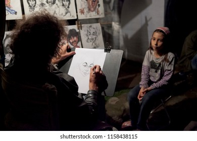 Paraty, Rio de Janeiro/Brazil - September 25, 2011: Sketch artists in the street drawing the face of a little girl in the evening with in the background drawings of famous people in a cartoonish style