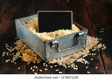 Parboiled rice with a small chalkboard in a box close up
