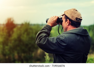 Parc ranger observes the hunting area trought his binocular