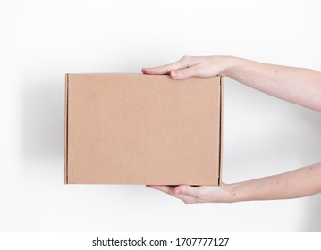 A parcel cardboard box in a delivery man hands on a white background. Delivery service concept.