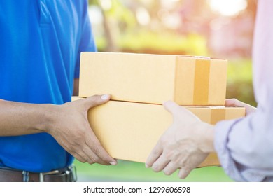 parcel delivery man of a package through a service. and close up hand customer accepting a delivery of boxes from delivery man postal.